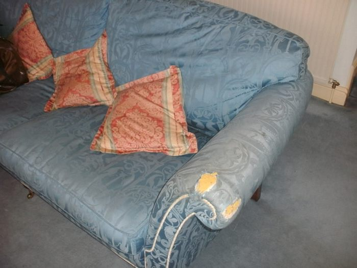 Sofa with worn out fabric on arms